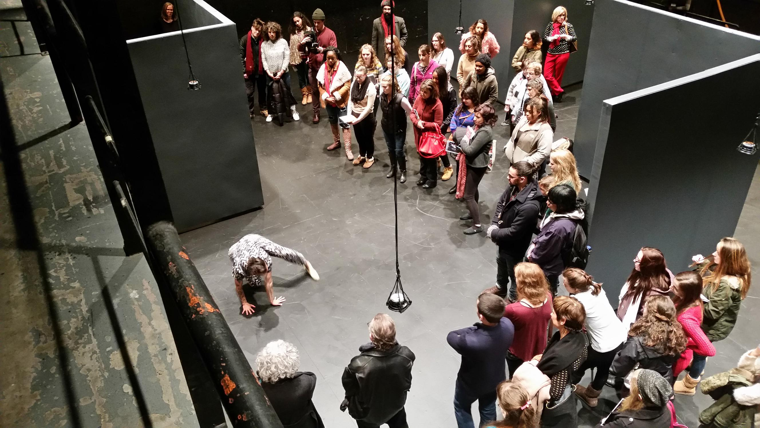 audience members watch the first performer as she begins to move-50%